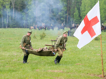 RUSSIA, CHERNOGOLOVKA - MAY 17: Unidentified men of medical squad move a wounded soldier on History reenactment of battle of Civil War in 1914-1919 on May 17, 2014, Russia