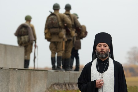 the godfather: RUSSIA, BORODINO - OCTOBER 12: Father Daniel, Dean of St. Nicholas Cathedral on reenactment of the battle in WWII near the Borodino village in 1941, in Moscow region, Borodino, on 12 October, 2014, Russia