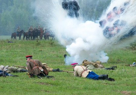 squad: RUSSIA, CHERNOGOLOVKA - MAY 17: Kornilovs hiking squad lying on grass and shoot  on History reenactment of battle of Civil War in 1914-1919 on May 17, 2014, Russia