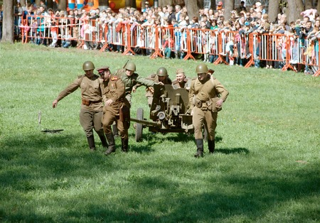 initiatives: ELECTROUGLI CITY - MAY 9: Soldiers wheel artillery cannon on reenactment of the last battle in WWII on celebration dedicated to The Victory day in World War II. This action created and shown by initiatives of Garnizon-A reenactment history club in Moscow