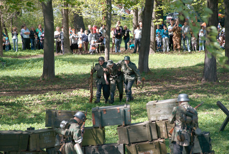 initiatives: ELECTROUGLI CITY - MAY 9: Wounded soldier walk to the others on reenactment of the last battle in WWII on celebration dedicated to The Victory day in World War II. This action created and shown by initiatives of Garnizon-A reenactment history club in Mosc Editorial