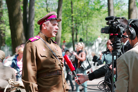 initiatives: ELECTROUGLI CITY - MAY 9: Timur Cherepnin gives an interview just before the reenactment of the last battle in WWII on celebration dedicated to The Victory day in World War II. This action created and shown by initiatives of Garnizon-A reenactment history