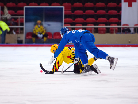 arbiter: MOSCOW - DECEMBER 12, 2014: Granovsky Vasily (25) fall down during the Russian  bandy league game Dynamo Moscow vs SKA Neftyanik in sport palace Krilatskoe, Moscow, Russia. Dynamo won 9:1