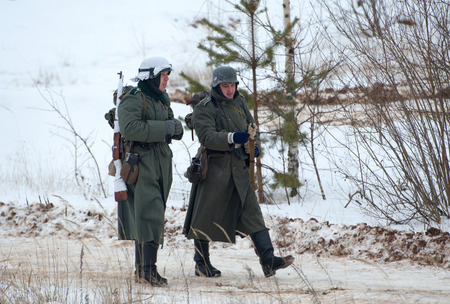 german soldier: RUSSIA, LIZLOVO - DECEMBER 14: Two unidentified German soldier walking on reenactment of the counterattack under the Moscow in 1941 in World War II, in Moscow region, Lizlovo village, Russia, 2014