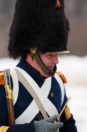 musketeer: RUSSIA, APRELEVKA - FEBRUARY 7: Unidentified russian musketeer smoking pipe on reenactment of the Napoleonic maneuvers near the Aprelevka city, in 1812. Moscow region, Aprelevka, 7 February, 2015, Russia
