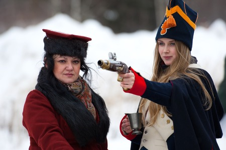 RUSSIA, APRELEVKA - FEBRUARY 7: Unidentified woman in retro costume shooting by gun on reenactment of the Napoleonic maneuvers near the Aprelevka city, in 1812. Moscow region, Aprelevka, 7 February, 2015, Russia Editorial