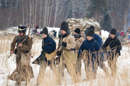 civilians: RUSSIA, APRELEVKA - FEBRUARY 7: Unidentified civilians armed with cudgel walk on reenactment of the Napoleonic maneuvers near the Aprelevka city, in 1812. Moscow region, Aprelevka, 7 February, 2015, Russia