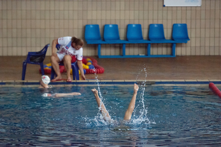 synchronous: RUSSIA, MOSCOW - APRIL 29 2015: Legs of unidentified synchronous swimer into the Pool on Moscow city diving tournament in Moscow, Russia, 2015 Editorial