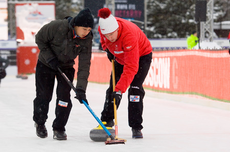 MOSCOW - JANUARY 17, 2016: Curling players M. Pfister (L) and S. Gempeler (R) in action during Russian Curling Champions Tour Moscow Classic 2016 on January 17, in Moscow, Russia, 2016