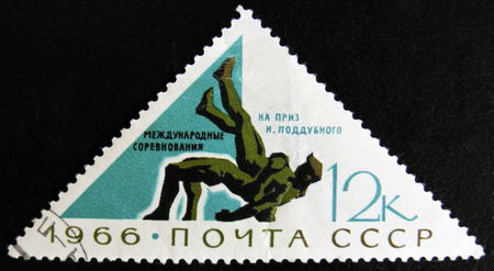 MOSCOW, RUSSIA - APRIL 2, 2017: A post stamp printed in USSR USSR shows two wrestlers, devoted to International wrestling competitions for the prize I. Poddubny, circa 1966
