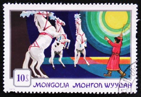 MOSCOW, RUSSIA - APRIL 2, 2017: A post stamp printed in Mongolia shows a trained horse rearing for a circus trainer, series Mongolian circuses, circa 1974
