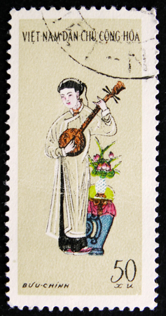 MOSCOW, RUSSIA - APRIL 2, 2017: A post stamp printed in Vietnam shows Woman playing banjo, circa 1975 Editorial