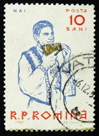 MOSCOW, RUSSIA - APRIL 2, 2017: A post stamp printed in Romania shows Peasants playing musical instruments, Panpipe, circa 1961