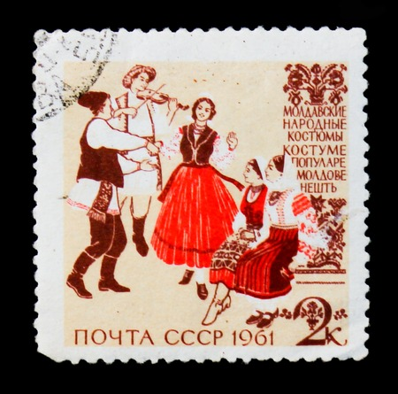 MOSCOW, RUSSIA - JUNE 26, 2017: A stamp printed in USSR (Russia) shows image of musicians and dancers in Moldovan traditional and historic folk costumes, from the series Folk costumes. circa 1961