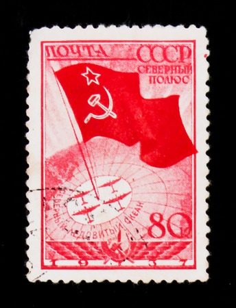 MOSCOW, RUSSIA - JUNE 26, 2017: Rare stamp printed in USSR (Russia) shows Flag with star, and polar planes on globe, circa 1937 Banque d'images - 101948079