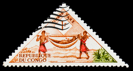 MOSCOW, RUSSIA - SEPTEMBER 3, 2017: A stamp printed in Congo shows Palanquin bearers, Ways of mail delivering serie, circa 1961