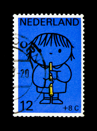 MOSCOW, RUSSIA - NOVEMBER 24, 2017: A stamp printed in Netherlands shows Child with flute, Children Stamps - Year of the Disabled serie, circa 1969