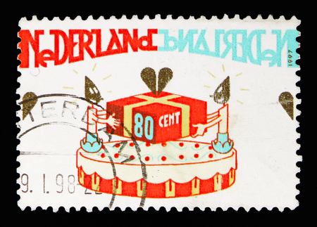 MOSCOW, RUSSIA - MAY 13, 2018: A stamp printed in Netherlands shows Birthday cake with present, Greetings Stamps serie, circa 1997