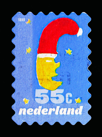MOSCOW, RUSSIA - MAY 13, 2018: A stamp printed in Netherlands shows Moon with Christmas hat, December stamps serie, circa 1999