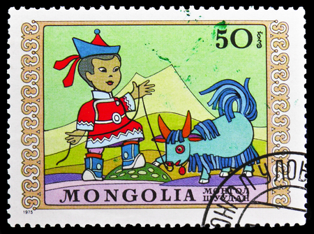 MOSCOW, RUSSIA - NOVEMBER 26, 2018: A stamp printed in Mongolia shows Boy and obedient little yak, International Children's Day serie, circa 1975 新聞圖片