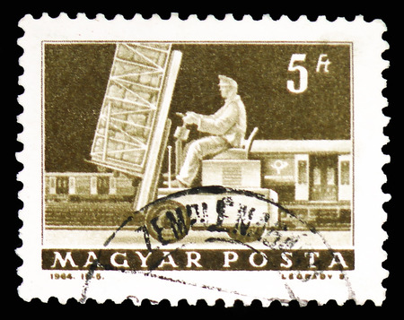 MOSCOW, RUSSIA - FEBRUARY 10, 2019: A stamp printed in Hungary shows Hydraulic lift truck and mail car, Transport and Telecommunication serie, circa 1964