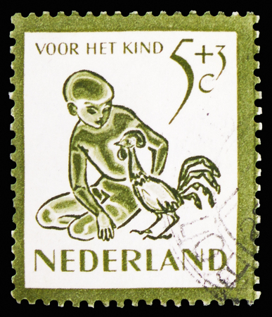 MOSCOW, RUSSIA - FEBRUARY 10, 2019: A stamp printed in Netherlands shows Child and animals, Children Stamps serie, circa 1950 Editorial