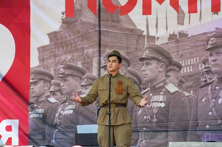 MOSCOW, RUSSIA - MAY 9, 2019: Unidentified man in military uniform sing a song on a scene during event dedicated to Victory Day on May 9, 2019