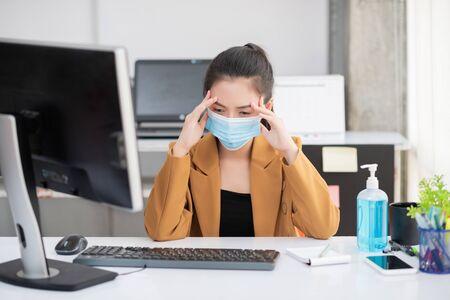 Les employés travaillant dans un bureau d'affaires ont eu des maux de tête et de la fièvre tout en portant un masque médical pour protéger et prévenir l'infection du virus corona ou du covid-19