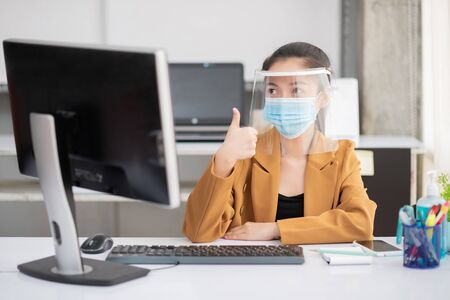 Employees working in the business office confident while wearing a mask and face shield for the prevention and prevention of coronary or Covid-19 virus infection.