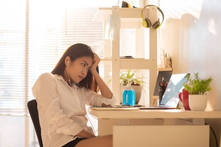 Asian women work at home according to government policies to prevent communicable diseases. This room receives bright orange sunshine and she is stressed about the job. 免版税图像