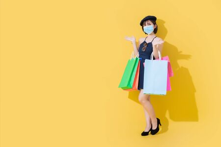 When the coronavirus or covid19 crisis improves.Cute Asian woman with both hands open. She wears a surgical mask and holds her hand. And carrying a shopping bag.This picture was taken in the studio. Which uses yellow and orange scenes under the concept of summer fashion.