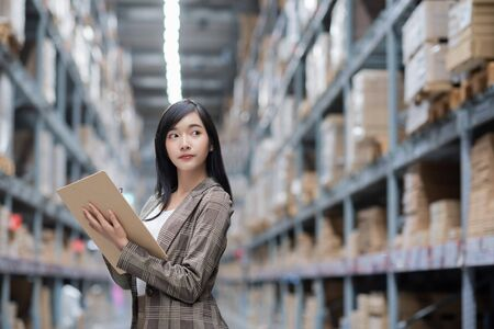 Asian woman worker of furniture store in shopping center. Girl looking for goods with a tablet is checking inventory levels in a warehouse. Logistics concept Imagens