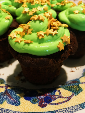 Chocolate cupcake with green frosting and golden stars sprinkles on a white mosaic-patterned plate Banco de Imagens