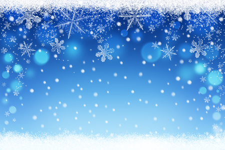 Beautiful blue blurred christmas and winter snow bokeh background with snowflakes