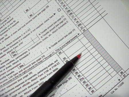 Red pen lies on copy of federal tax form Reklamní fotografie