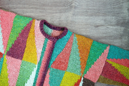 Colorful white, yellow, brown, pink, green, blue, turquoise, orange, claret handmade knitted wool cardigan on the wooden background Intarsia pattern Rustic wool