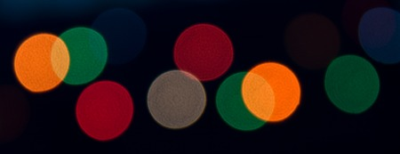 Christmas or Halloween vivid abstract concept. Bright spots of red, yellow, green and blue lights on blackground. Bokeh. Soft focus. Round shapes. WEb banner Stock Photo
