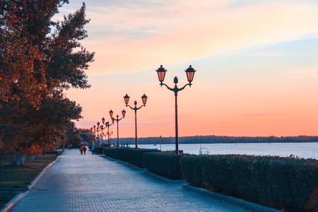 People walking at the sunset in Samara city embankment. Autumn fall time