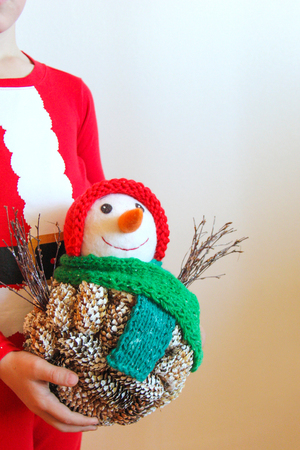 Child dressed in red Christmas pajamas holds in hands a self-made snowman of fir cones and wool with a knitted red hat and a green scarf