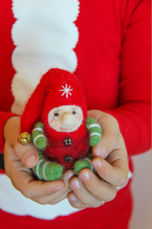 Child dressed in red Christmas pajamas holding in hands an elf made of red, white and green wool with a golden bell on the cap 版權商用圖片