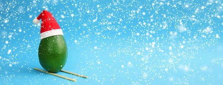 Christmas decoration snowfall background idea with fresh green avocado skiing in santa hat on snow drifts on bright blue background with snow flakes. Stock Photo