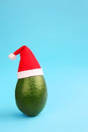Christmas decoration background idea with frsh green avocado in santa hat on bright blue background.