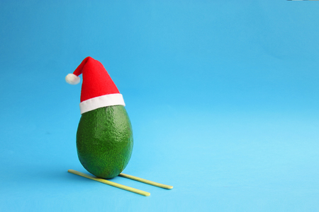 Christmas decoration background idea with frsh green avocado skiing in santa hat on bright blue background.