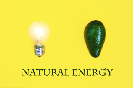 Fresh harvest green avocado as a source of vital energy next to a light bulb close up, isolated on yellow background.