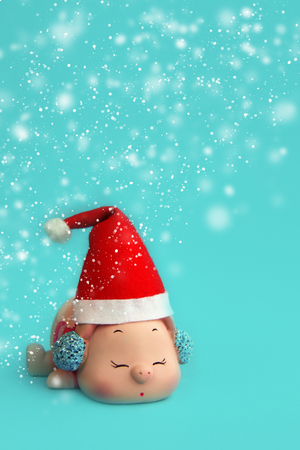 Nice pink pig in red Santa hat as New Year decoration background with snowflakes on blue paper background. Card concept. Closeup. Front view. Copy space