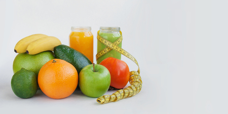 Creative background smoothie juice persimmon,lime,suite,avocado,apple,orange banana tape measure white paper. 免版税图像
