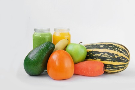 Creative background smoothie juice summer fruits vegetables. Avocado,apple, carrot banana persimmon zucchini white paper.