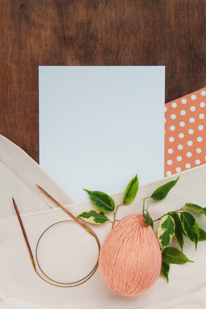 Beautiful background of coral and white paper polka dot with wool ball of egg yarn, wooden knitting needles, branch of ficus benjamin a beige plaid on a wooden background with copy space. Top view