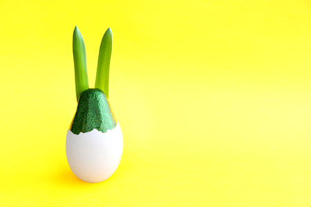 Beautiful creative decoration background idea with fresh green avocado rabbit hatching from an egg on bright yellow paper. Card concept.Holiday decorative theme.Closeup.Front view. Copy space Stock Photo