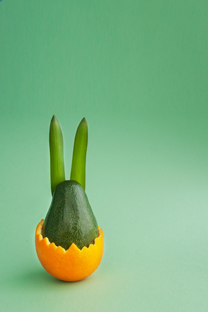 Beautiful creative decoration background idea with fresh green avocado rabbit hatching from orange skin on bright green paper. Card concept.Holiday theme.Closeup.Front view. Copy space Banque d'images - 116368579